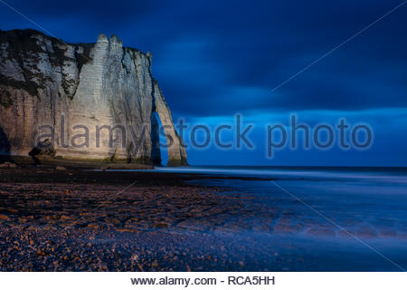 At dusk, English Channel waves crash through a natural sea arch known as Porte d'Aval at the Falaise d'Étretat cliffs in Normandy, France. The white c - Stock Photo