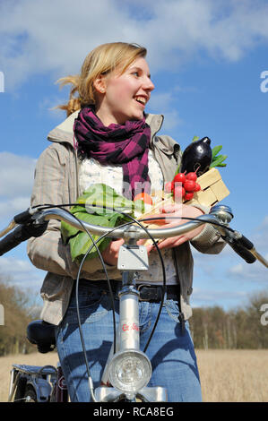 junge Frau mit Fahhrad und Gemüsekorb - junges Gemüse   young women with her bycicle and vegetable basket - Stock Photo