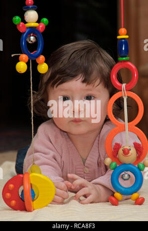 Baby im Zimmer liegt auf dem Boden, Spielzeug | baby lying in a room on the floor, playing with toys - Stock Photo