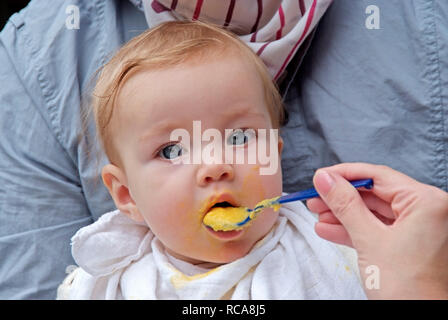 Eltern füttern ihr Baby mit Brei | parents feeding their baby wit pap - Stock Photo