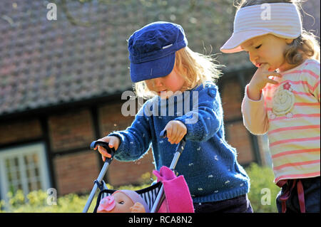 Kinder spielen mit Kinderwagen | Children playing with a buggy - Stock Photo