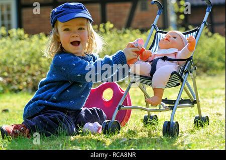 kleines Mädchen, 2 Jahre alt, kümmert sich um ihre Puppe im Puppenbuggy | little girl, 2 years old, taking care of her doll - Stock Photo
