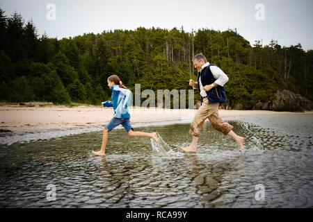 Young girl running along a beach with her grandfather. - Stock Photo