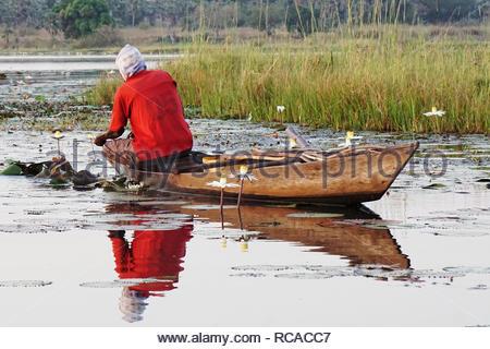 fisherman fishing in a little boat on the lake tengrela in africa, burkina faso - Stock Photo