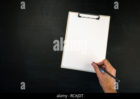 Writing on clipboard, male hand with pencil and blank page as copy space - Stock Photo