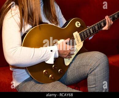 Woman playing a electric guitar. Closeup, no face. - Stock Photo