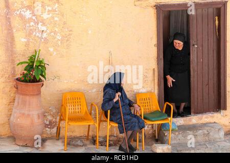 Two elderly Greek ladies, dressed in black, chatting outside a village house in Pano Elounda, Crete, Greek Islands, Greece - Stock Photo