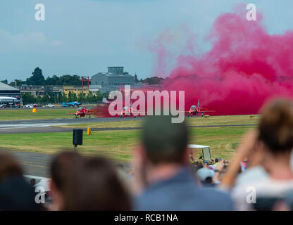 Crowds watch the Red Arrows as they take off to start their display at the Farnborough Airshow, Farnborough, Hampshire, England, UK - Stock Photo