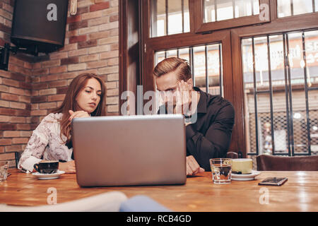 Two worried employees reading bad news together on line in a laptop in cafe- Image. Problems at work place. Negative face expressions, emotions. - Stock Photo