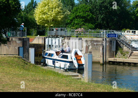 Motor boat entering Mapledurham Lock on the River Thames on a summer's day near the village of Purley-on-Thames, Berkshire, England, UK - Stock Photo