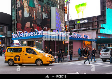 New York City, United States - November 17 2018:   A Yellow New York Taxi driving past a New York Police Department station on Broadway - Stock Photo