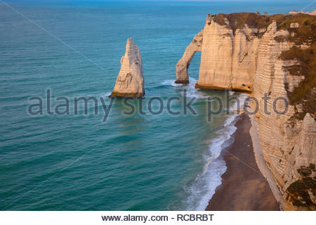 The sea arch Porte d'Aval and the sea stack L'Aiguille (the Needle) stand in the Atlantic Ocean next to the cliffs of Étretat in Normandy, France. - Stock Photo