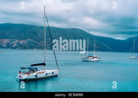 Yachts anchored near beautiful greek shoreline, on an overcast day in summer, coastal, travel, vacation concept - Stock Photo