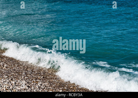 Waves rolling in on Greek beach - Stock Photo