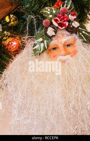 Decorated Santa Claus doll hung on the staircase handrail inside a home - Stock Photo