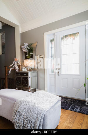 Ottomans, metal and glass topped mirror cabinet and Christmas decorations in entryway inside an old renovated circa 1840 Canadiana cottage style home - Stock Photo