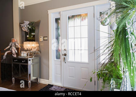Metal and glass topped mirror cabinet and Christmas decorations in entryway inside an old renovated circa 1840 Canadiana cottage style home - Stock Photo