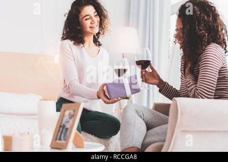 Attentive sister making surprise for her loving sibling - Stock Photo