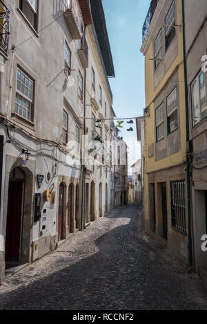 A cobblestone alleyway leading down between typical buildings with Fado bar and wall and hanging street decorations in Coimbra Portugal - Stock Photo