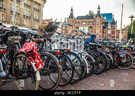 View of bicycles along street in Amsterdam with historic Stadsschouwburg building in the background - Stock Photo
