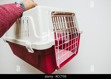 Man hand holding against white background animal pet cage used for cat and dog transportation in planes and buses - Stock Photo