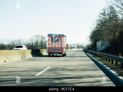 ACHERN GERMANY - FEB 18, 2018: Driving in front Deutsches Rotes Kreuz ambulance on German rural road - Stock Photo