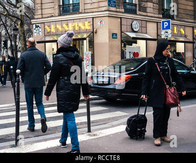 PARIS, FRANCE - JAN 30, 2018: French male and female crossing street in front of Mercedes -Benz luxury limousine in Paris, on the Rue St Vincent de Paul - Stock Photo