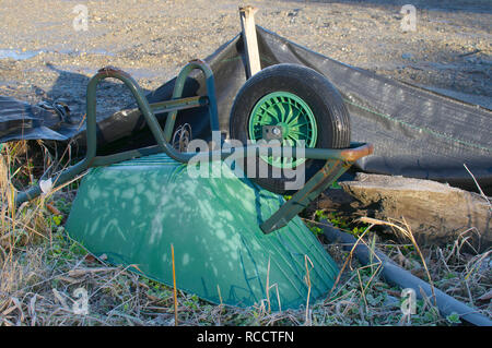 An green abandoned wheelbarrow upside down in an empty construction site in British Columbia, Canada. - Stock Photo