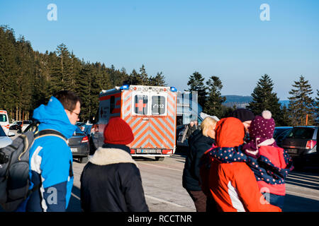 SEEBACH MUMMELSEE, FEB 25, 2018: Deutsches Rotes Kreuz ambulance in German parking with people crossing street in German mountains - Stock Photo