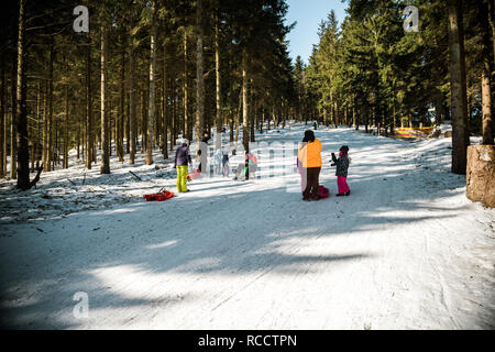 SEEBACH MUMMELSEE, FEB 25, 2018: Adults and kids sleighing the sledding slope on a sunny winter day in Black Forest, Baden Wurttemberg - Stock Photo