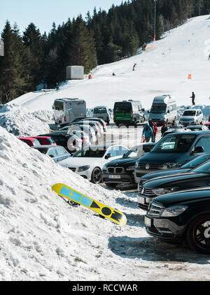 SEEBACH MUMMELSEE, FEB 25, 2018: Parking in Black Forest mountains with ski slope in background and snowboard near cars - Stock Photo