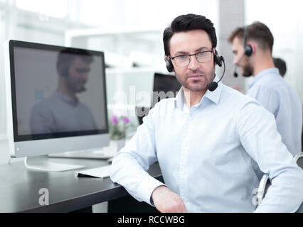 confident call center Manager sitting in front of computer screen - Stock Photo
