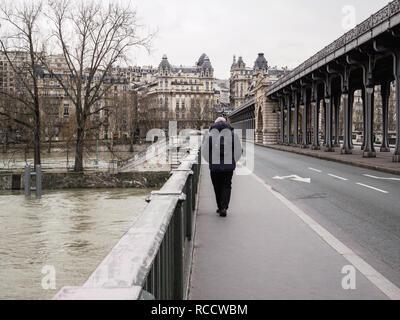 PARIS, FRANCE - JAN 30, 2018: Rear view of man walking on pedestrian part of the BirHakeim bridge in Paris during Seine floodings - Stock Photo