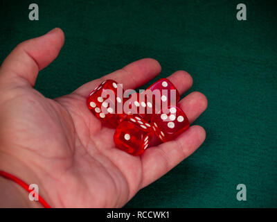 The hand of a person throwing the dice on a green carpet - Stock Photo