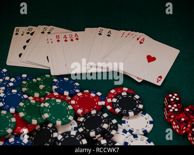 A poker deck, poker chips of different colors and several dice on a green mat - Stock Photo