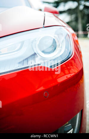 PARIS, FRANCE - NOV 29, 2014: New red Tesla Model S detail of the bi-xenon led headlight lamps on the red painted car - Stock Photo