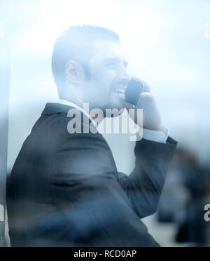 employee talking on the phone, sitting on the windowsill - Stock Photo