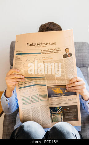 Paris, France - Mar 16, 2018: Young business woman reading Financial Times newsletter with main articles about Markets and investing - Stock Photo