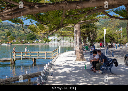 Akaroa, New Zealand, January 6 2019: tourists enjoy the view of the bay on a hot summer evening - Stock Photo