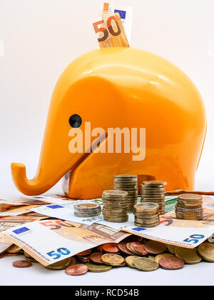 Image of pile of Euro coins with yellow piggy bank in the background close up - Stock Photo
