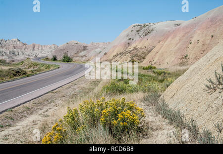 Scenic Drive in South Dakota:  A road in Badlands National Park curves among jagged  formations, blooming wildflowers and arid hills in rainbow colors - Stock Photo