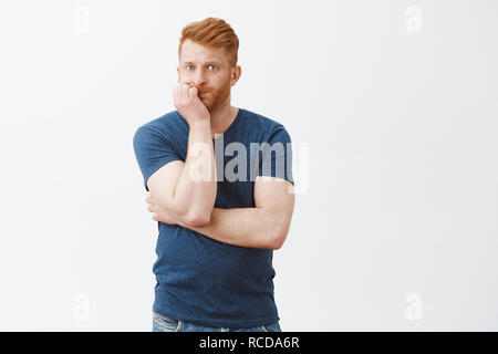 Intense nervous and shocked man trying to sit still in cafe so girlfriend would not see him dating another woman, holding breath, pursing lips, leaning on fist and staring anxiously at camera - Stock Photo