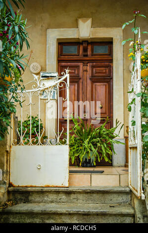 Looking up steps at house large double wooden doors with two small windows above door and gated patio with green plants - Stock Photo