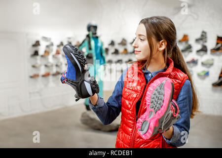 Young woman choosing trail shoes for mountain hiking in the modern sports shop