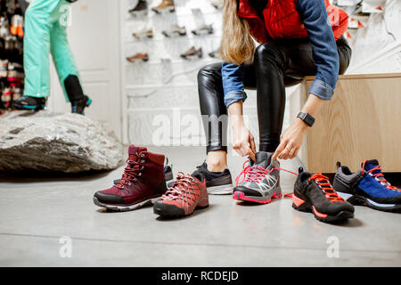 Woman trying different trail shoes for mountain hiking in the sports shop, close-up view with no face