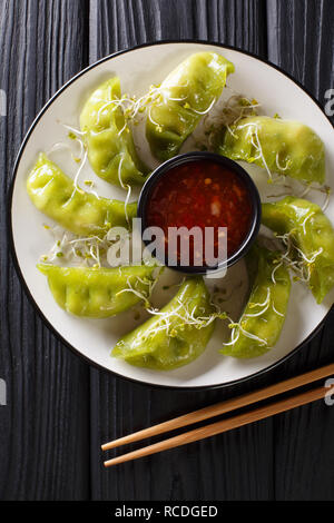 Fresh green gyoza dumplings with matcha are served with spicy chili sauce and microgreen close-up on a plate on the table. Vertical top view from abov - Stock Photo