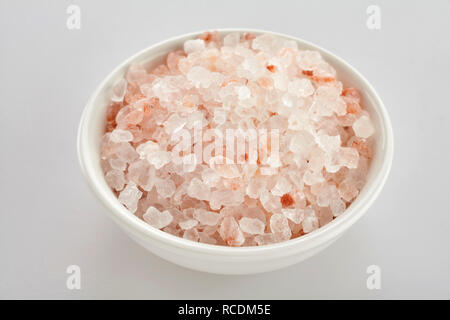 Bowl of coarse pink Himalaya salt, a rock salt or halite used for seasoning food, over a white background - Stock Photo