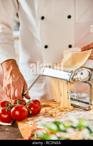 Chef cutting raw dough on a pasta cutter making homemade spaghetti with fresh ingredient foreground - Stock Photo