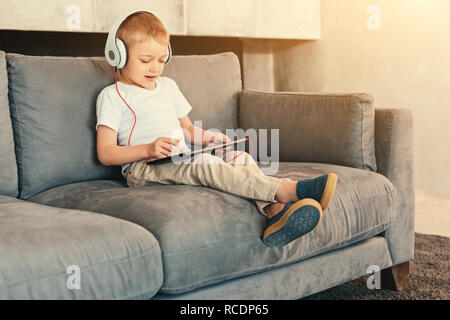 Technology lover. Cute little boy sitting on the sofa and playing a game on the tablet while listening to the game sounds in headphones - Stock Photo