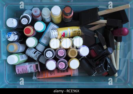 A plastic container full of acrylic paints, foam brushes, and rollers, as seen from above. - Stock Photo
